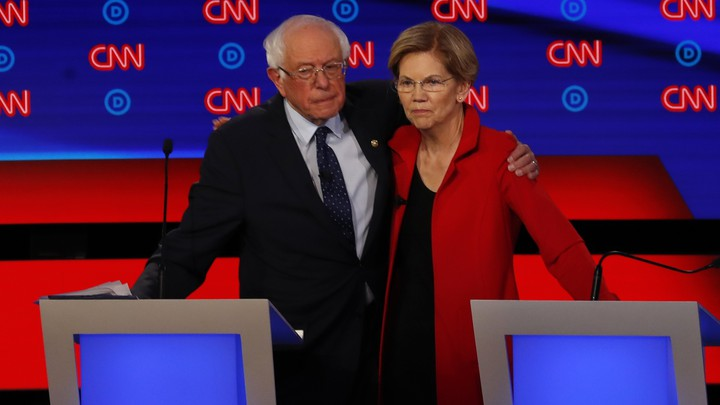 Bernie Sanders puts an arm around Elizabeth Warren.