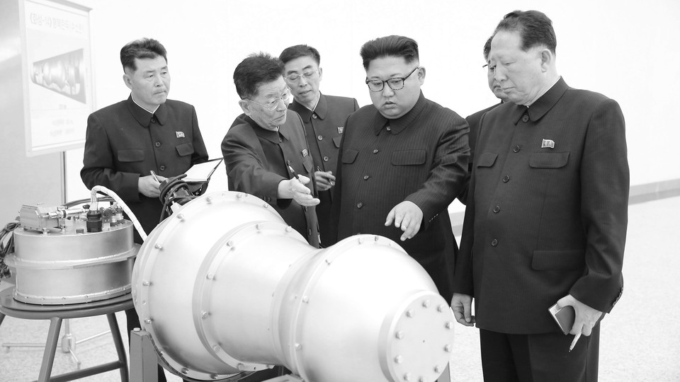 Kim Jong Un looking at machinery with advisers