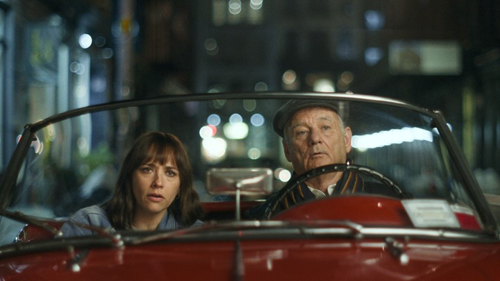 Rashida Jones and Bill Murray in a red roadster