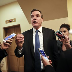 Virginia Senator Mark Warner speaks with reporters carrying cell phones.
