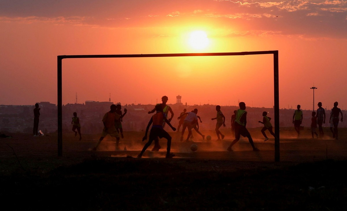 People play soccer on a dusty field at sunset.