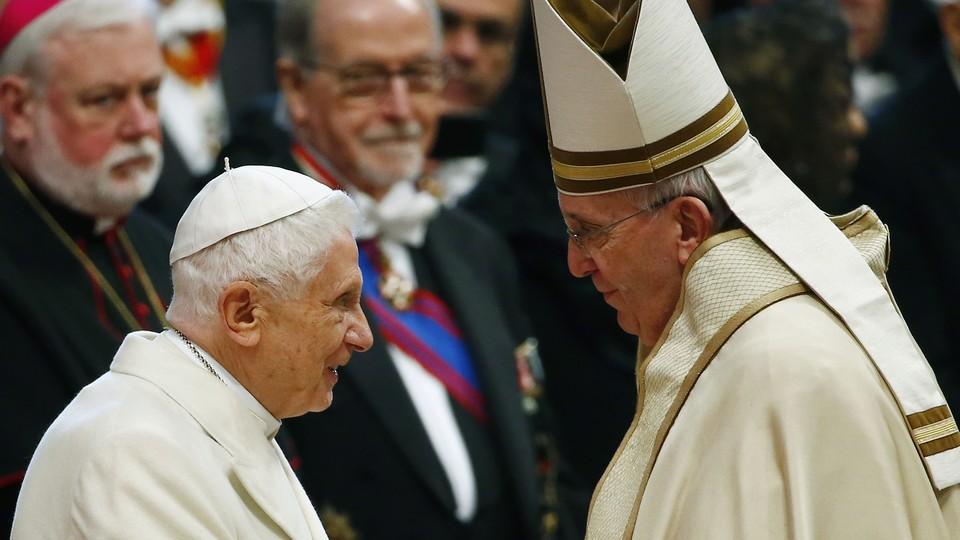 Pope Francis greets Pope Emeritus Benedict XVI.