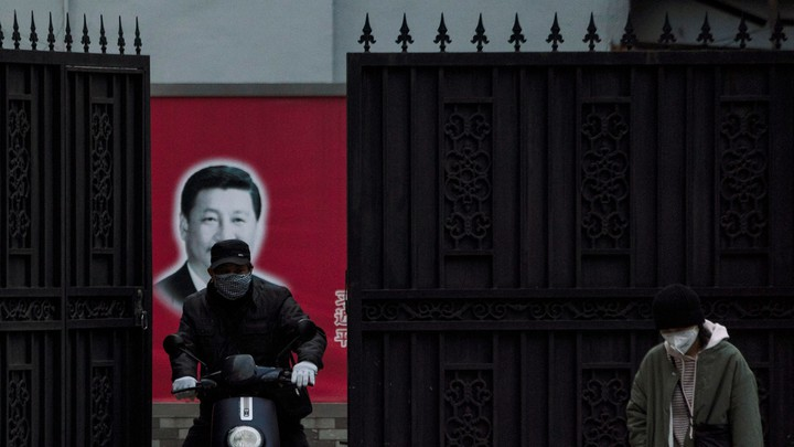 A masked man on a scooter in front of a portrait of Xi Jinping