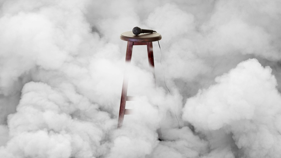 A wooden stool with a microphone on top, surrounded by smoke