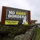 "A billboard erected at the Irish border reads ""No hard border: Border Communities Against Brexit."""