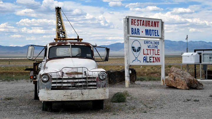 A tow truck parked beside a sign for the Little A'Le'Inn in Rachel, Nevada