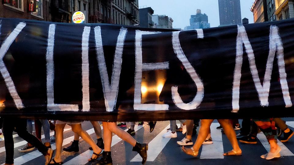 People walking across a crosswalk behind a Black Lives Matter banner