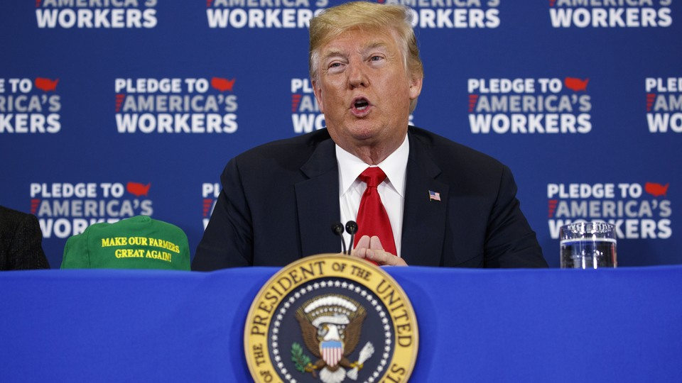 """President Donald Trump sits at a blue table with a """"Make Our Farmers Great Again"""" hat"""