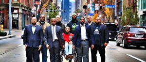 Leon Ford, center, in a wheelchair, is surrounded by friends and colleagues in Pittsburgh.