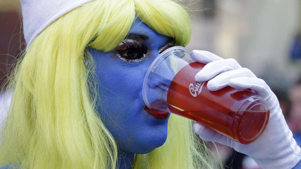A person in a yellow wig and blue face paint drinks out of a plastic cup.