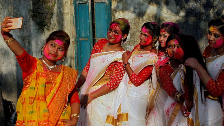 A group of women with colored powder on their faces take a selfie with a smartphone.