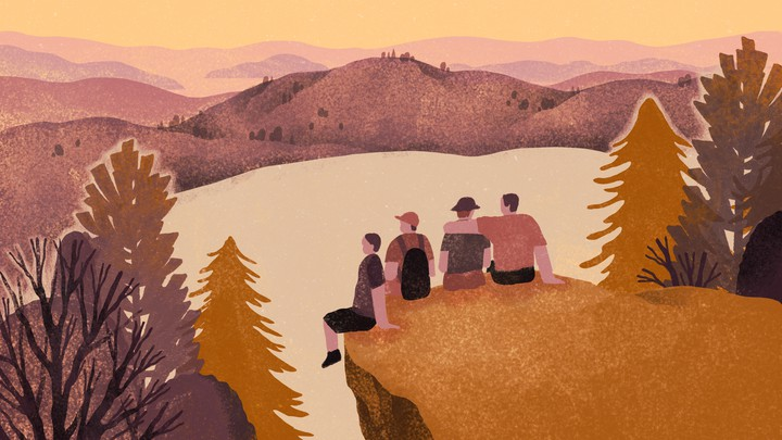 A group of four friends set on a cliff overlooking a lake in the woods