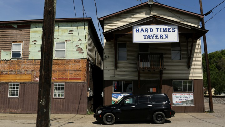 "A rustic building with a sign that says ""Hard Times Tavern"""