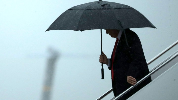 Donald Trump stands underneath an umbrella.
