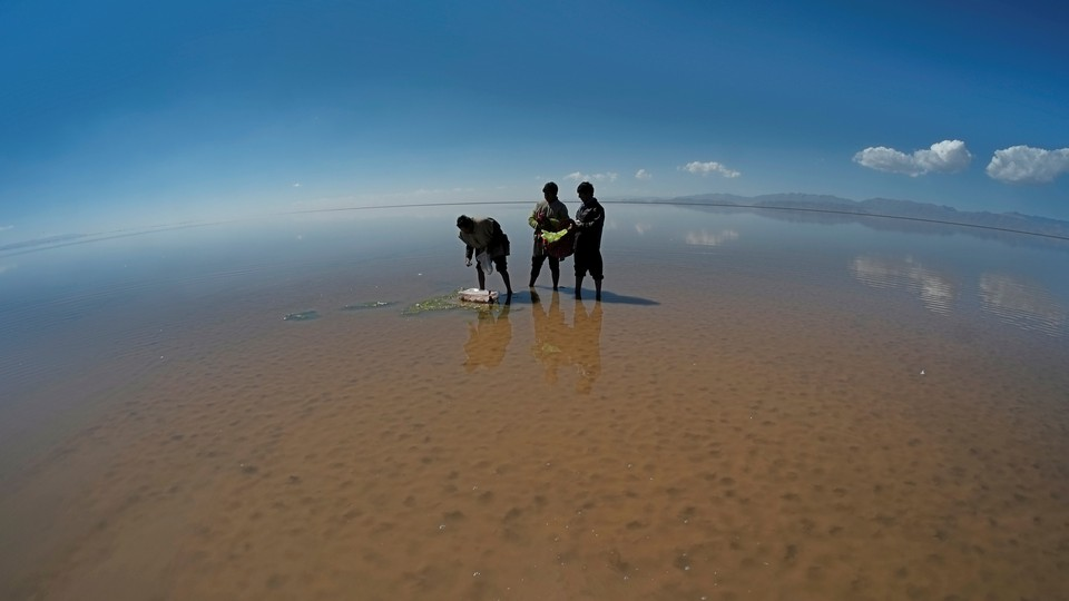 Men perform a ceremony on the drought-stricken bed of Poopó, a lake in Bolivia.