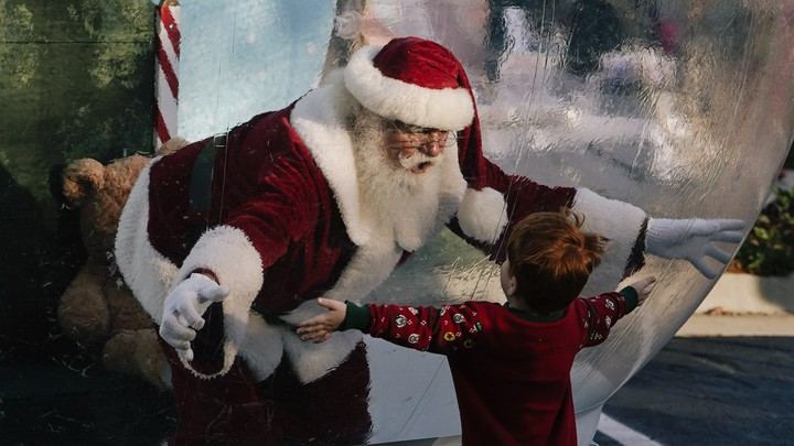 Santa Claus, entrapped in a giant snow globe, reaches out his hands towards a little boy, who also has his arms outstretched.