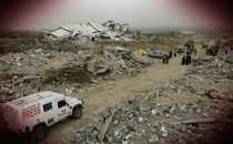 A Reuters truck drives through a bombed refugee camp in Gaza.