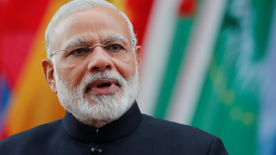 India's Prime Minister Narendra Modi looking at the camera in front of a row of flags.