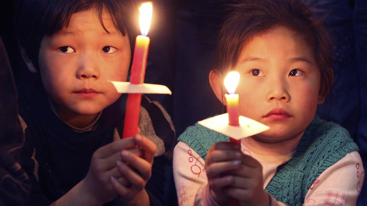 Children hold candles during the Easter mass at a church in Xiaohan village of Tianjin municipality in 2009.