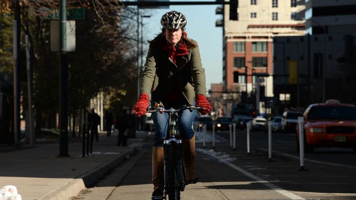 A woman rides a bicycle down a bike lane in Denver