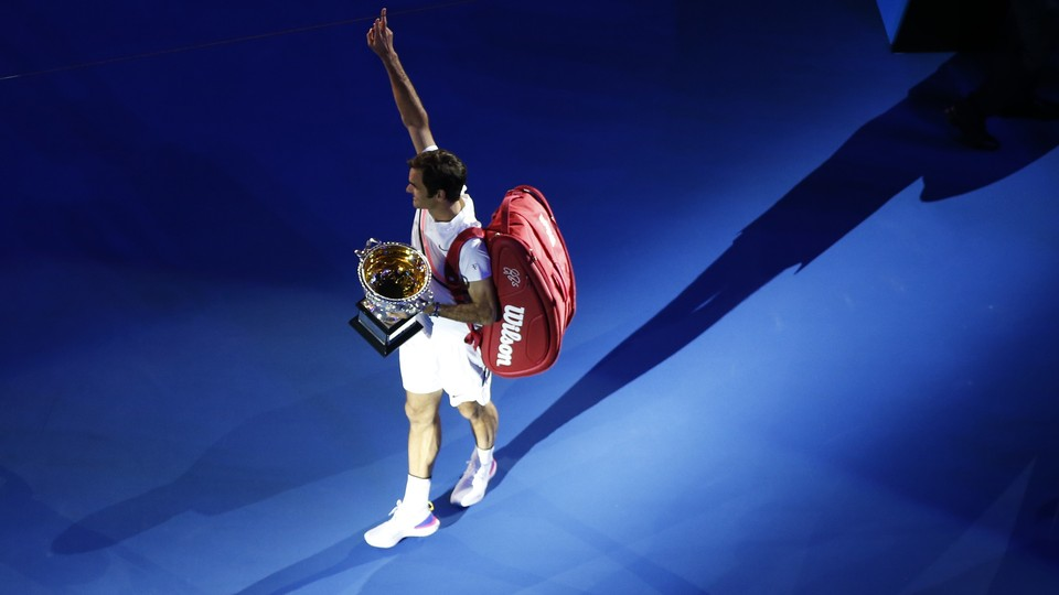 After the Australian Open men's singles finals, the winner Roger Federer of Switzerland celebrates with the trophy