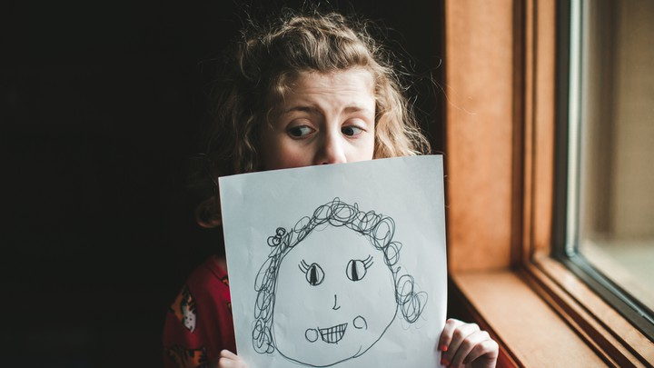 A little girl holds up a picture of herself that she has drawn.