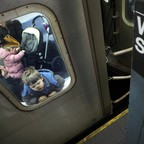 A boy presses his face against the glass of a subway car at the Wall Street station in New York