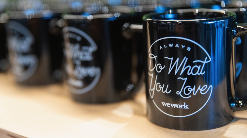 A row of coffee mugs imprinted 'Always Do What You Love  — WeWork'