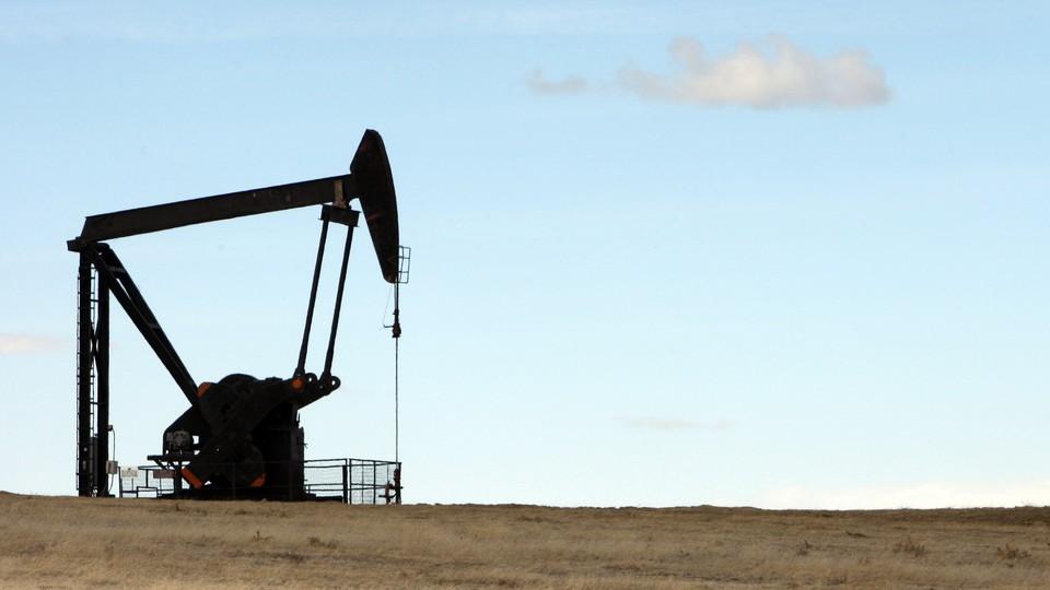 A crane-like machine drills into a field for oil