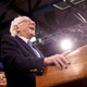 Bernie Sanders laughing at a podium