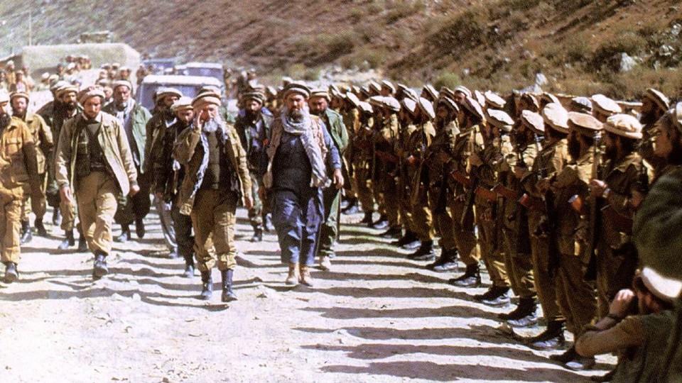 Abdallah Azzam walks down a road in Afghanistan.