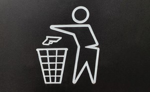 """Sign with """"Don't Litter"""" sign-style outline of person throwing gun into trash"""