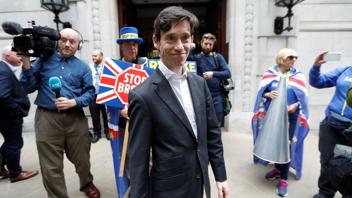 """Rory Stewart emerges from TV studios in Westminster, London. A protester holding a sign reading """"Stop Brexit"""" stands in the background."""