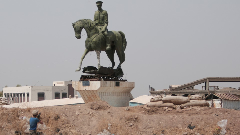 A Kurdish fighter fires a weapon at a statue of Bassel al-Assad, Bashar al-Assad's brother, in Hasaka, Syria, in August 2016.
