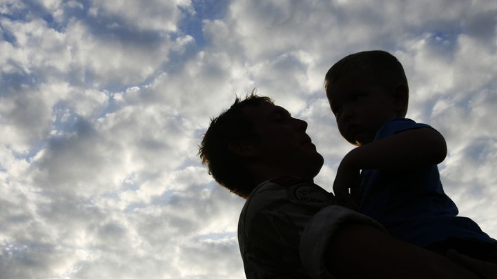 The silhouette of a father holding his son with a cloudy blue sky in the background