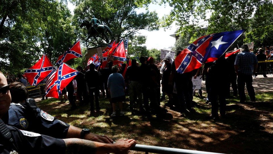 A group surrounds a statue while carrying Confederate flags.