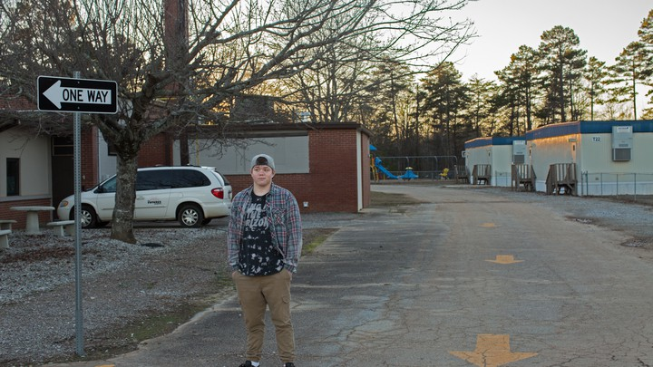 "A 16-year-old boy wearing a backward baseball cap, flannel shirt, and khakis stands in front of trailers and a ""one way"" sign with his hands in his pockets."