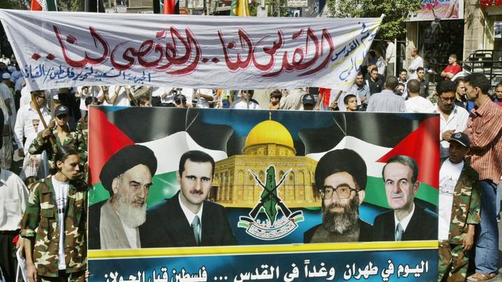 Protestors hold up a banner picturing late Ayatollah Ruhollah Khomeini, Syrian President Bashar al-Assad and Iranian Supreme Leader Ali Khameni and late Syrian Presidnet Hafez al-Assad.