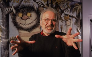 Maurice Sendak makes a gentle spooky gesture in front of his illustrations.