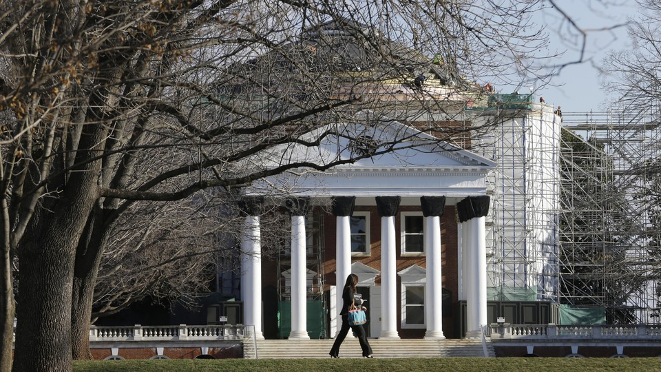 A woman walks past a building on the University of Virginia campus.