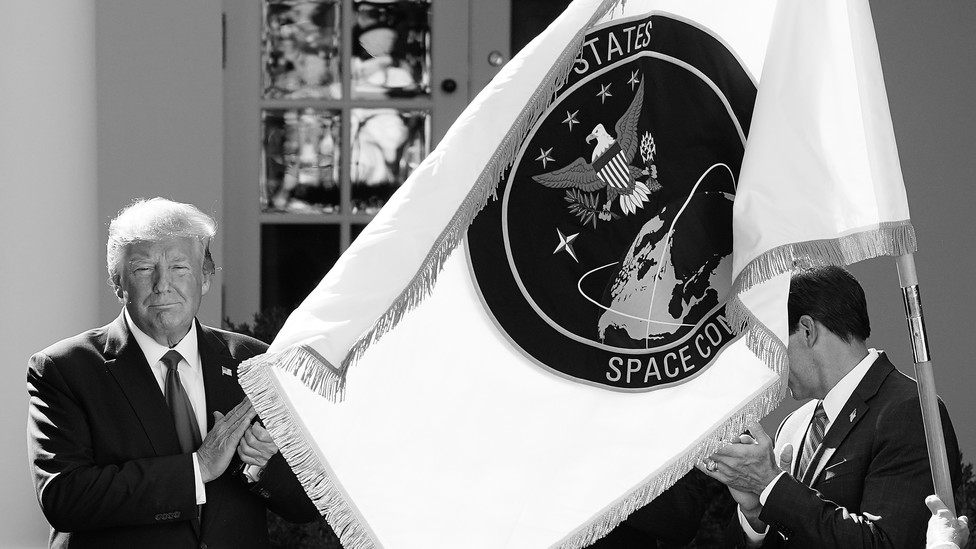 Former President Donald Trump poses with the flag of the U.S. Space Command
