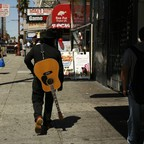 A man walks on the street with a guitar on his back.