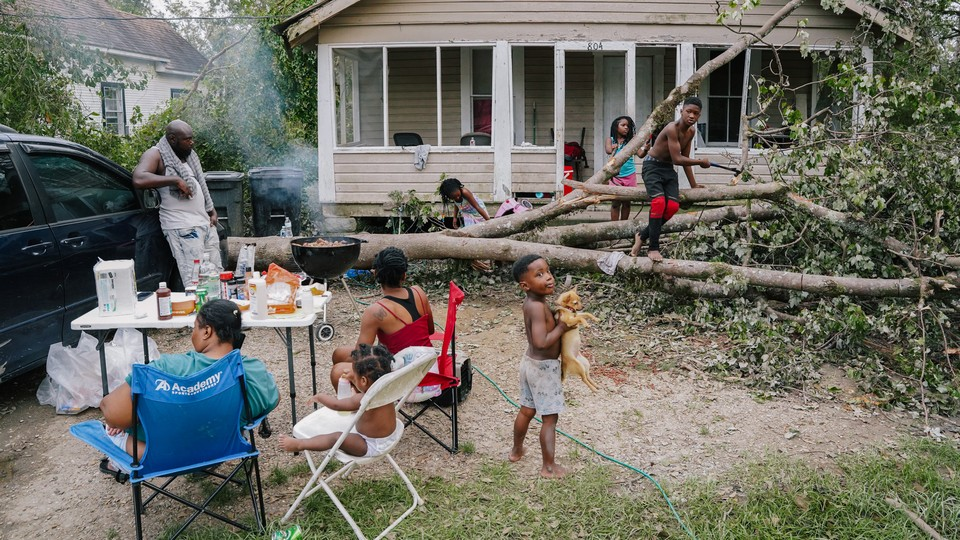 A famile prepares dinner in their front yard after Hurricane Ida.