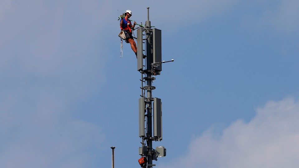 A worker atop a mobile-phone tower