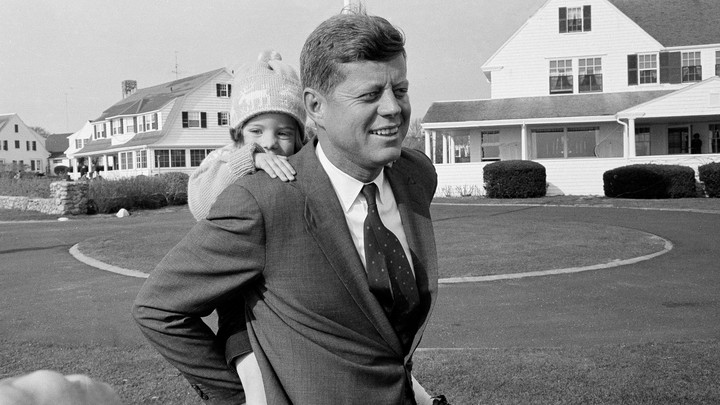 John F. Kennedy with his daughter on his back