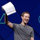 Mark Zuckerberg holds a stack of papers aloft, against a blue background.