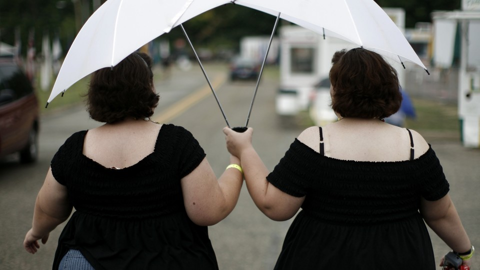 Two women dressed in black dresses holding white umbrellas