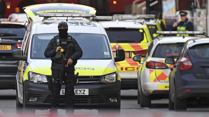 An armed police officer stands in front of a police car in the London Bridge area of the British capital.
