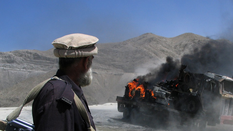 A Pakistani security official stands near a burning vehicle after it was attacked in the Balochistan region.