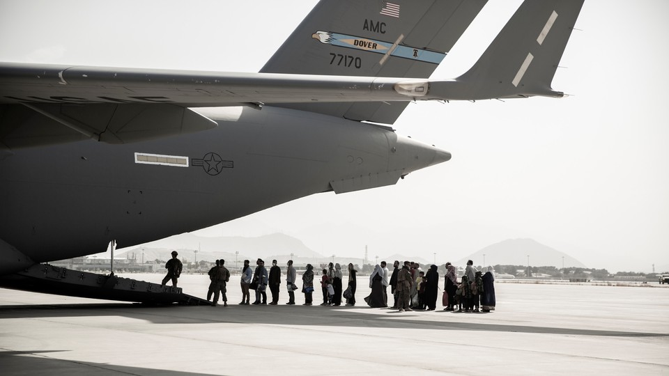 People wait to board a military plane.